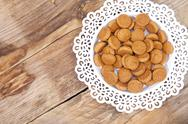 Traditional Dutch candy pepernoot on white plate on wooden background Stock Photos