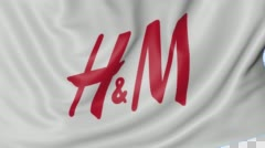 Close up of waving flag with H&M logo, seamless loop, blue background. Editorial Stock Footage