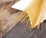 Pile of spelt spaghetti on white platen on wooden table Stock Photos