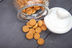 Little pile of tradtional Dutch candy pepernoten with glass jar and heart cov Stock Photos