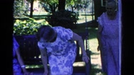 1966: woman moves over to make room for third lady on front porch swing Stock Footage