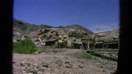 1966: abandoned western mining town with buildings set against rocky hillside Stock Footage