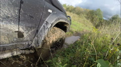 The car rides through the mud on the descent to the river. Off-road. Stock Footage