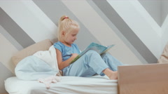 Cute little child girl wearing pajama reading a book on a bed under a blanket Stock Footage