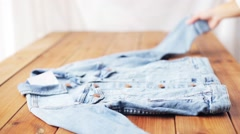 Woman folding denim jacket on wooden table at home Stock Footage
