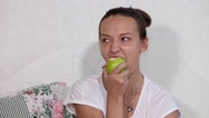 Beautiful woman giving bite to green apple Stock Footage