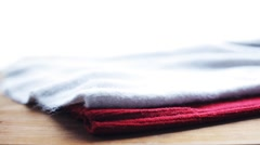 Knitwear or woolen clothes on wooden table at home Stock Footage