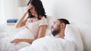 Angry woman waking man sleeping in bed Stock Footage
