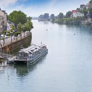 Navigable river, urban promenade and pleasure vessel Stock Photos
