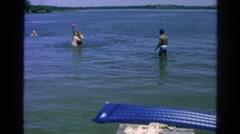 1966: lake summer fun throwing ball in water dad on dock pier CALIFORNIA Stock Footage
