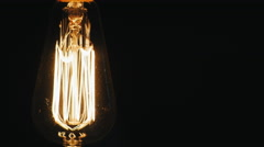 Oblong Vintage lamp Edison. Slowly turn on a black background. Near the free Stock Footage