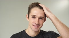 Closeup of young handsome man preens before the mirror in studio on white Stock Footage
