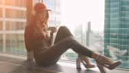 Cute girl sitting by window listening to music with headphones and sending sms Stock Footage
