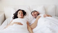 Happy couple awakening in bed at home Stock Footage