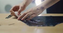 The girl designer works with garment component varnished leatherette Stock Footage