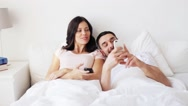 Happy couple with smartphones in bed Stock Footage