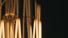 Macro spiral light bulb. Slowly turn on. On a black background Stock Footage