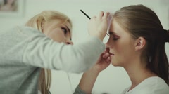 Make-up artist puts a brush for makeup to the eye model. Feather Stock Footage