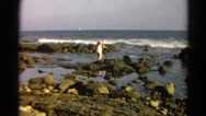 1966: woman wading through the rocky water on the coast CALIFORNIA Stock Footage