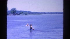 1966: father and mother and two female children throwing red ball in lake  Stock Footage