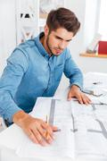 Young casual businessman working with documents Stock Photos