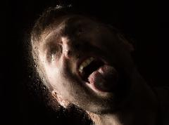 Drops of water on a glass, hand and male face. adult man standing at the window Stock Photos