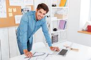 Smiling happy businessman standing at the office table Stock Photos