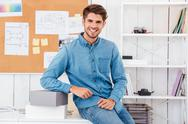 Man sitting on the office desk with boxes Stock Photos