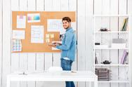 Smiling young man holding laptop and standing at task board Stock Photos