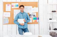 Cheerful man standing at the task board and holding laptop Stock Photos