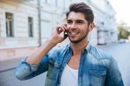 Happy man talking on cell phone outdoors Stock Photos