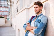 Man standing with arms folded and leaning on the wall Stock Photos