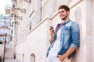 Smiling happy casual man using mobile phone outdoors Stock Photos