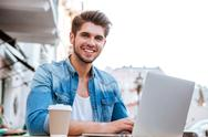 Smiling casual man using laptop while sitting at cafe outdoors Stock Photos