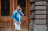 Happy smiling man talking on the mobile phone while walking Stock Photos