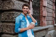 Student talking on the mobile phone and drinking coffee Stock Photos