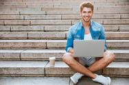 Man student using laptop while sitting on the staircase outdoors Stock Photos