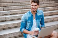 Man with laptop drinking take away coffee on the staircase Stock Photos
