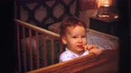 1973: shy and beautiful child standing on his cradle in his bedroom LYNBROOK Stock Footage