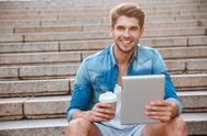 Happy cheerful student with tablet and coffee cup sitting outdoors Stock Photos
