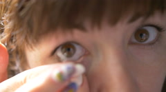 Woman looking into the camera and wears contact lenses close-up Stock Footage