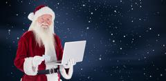 Composite image of santa pays with credit card on a laptop Kuvituskuvat