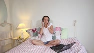 Happy young girl watching a movie on laptop at home Stock Footage