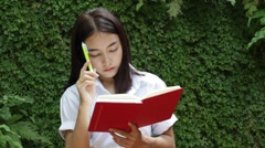 Thai adult student university beautiful girl reading red book Stock Footage
