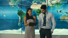 4K Business team in control room with large world map graphic on video wall Stock Footage