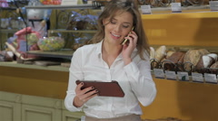 Woman talks on the phone at the pastry shop Stock Footage