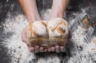 Bakery concept background. Hands hold bread loaf Stock Photos
