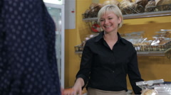 Female seller gets credit card from the client at the pastry shop Stock Footage