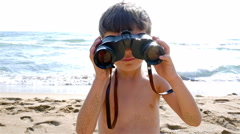 Little boy in swimsuit uses binoculars to explore the sea Stock Footage