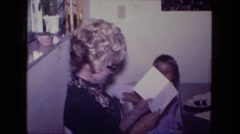 1976: middle aged women with blonde curly hair opening birthday card gift  Stock Footage